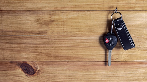 Car key with remote control hanging at wooden wall.