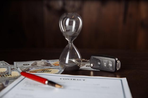 木製の部屋で署名された契約書の車のキーと砂時計。
