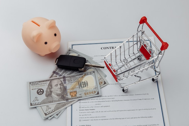 Car keys, dollar banknotes and piggy bank on credit contract.