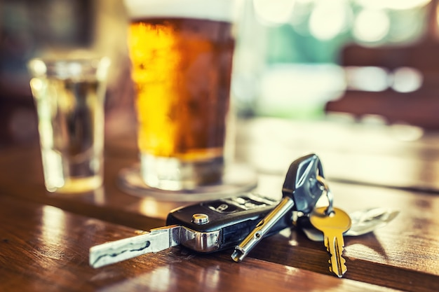 Car keys and glass of beer or distillate alcohol on table in pub or restaurant.