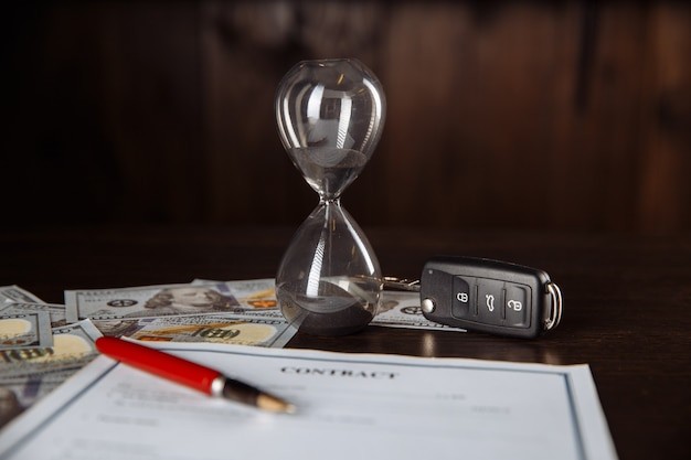 Car keys and hourglass on the signed agreement document in wooden room.