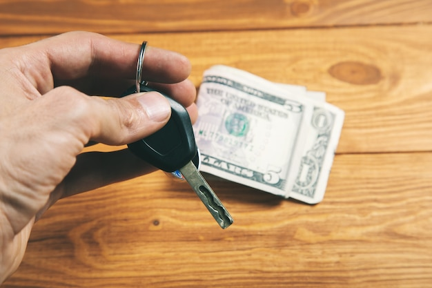 Car keys and money buying a car mobile