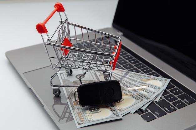 ノートパソコンのキーボードにドル紙幣とショッピングカートが付いた車のキー。オンライン購入車のコンセプト