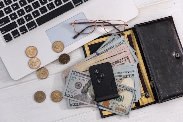노트북 키보드에 달러 지폐가 있는 자동차 키, 판매 개념