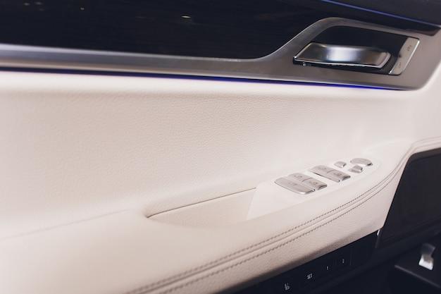 窓のコントロールと調整を備えたドアハンドルのカーレザーインテリアの詳細。車の窓のコントロール。