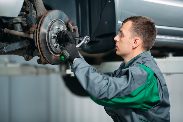 Car lifted in automobile service for fixing and worker repairs the wheel
