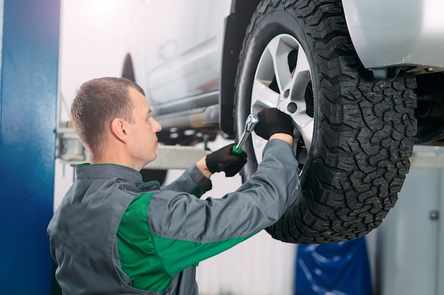Car lifted in automobile service for fixing, worker repairs the wheel