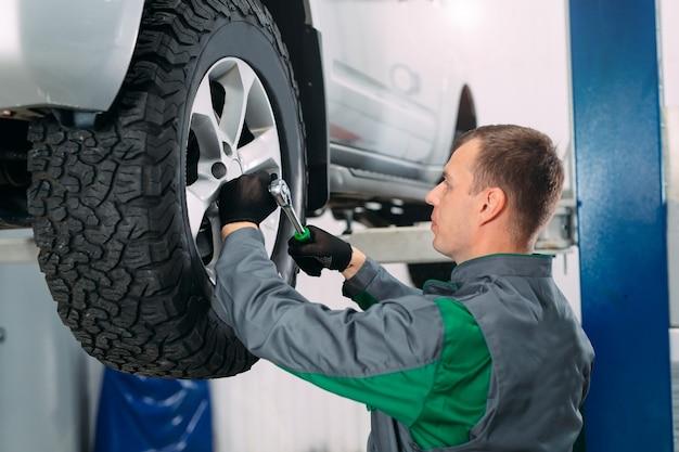 自動車の修理で持ち上げられた車の修理および作業員によるホイールの修理