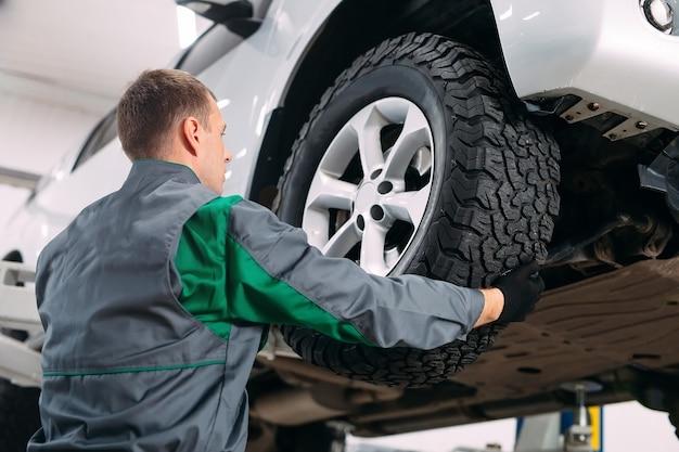 Автомобиль подняли в автосервис для ремонта, рабочий ремонтирует колесо