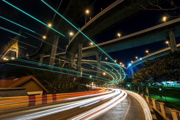 Car light trail on local street under bhumibol bridge in bangkok, thailand.