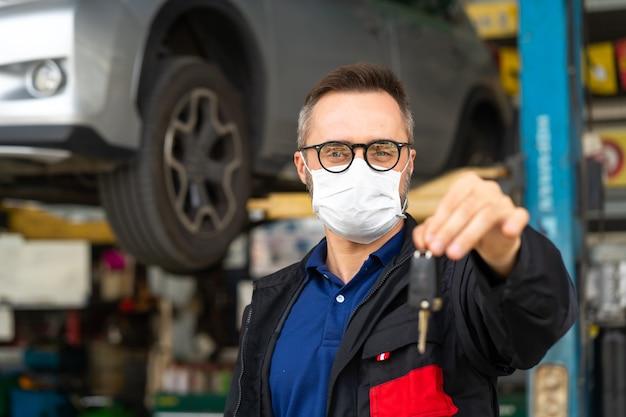 Автосервис и гараж автосервиса. портрет мужчины-менеджера бороды дает ключ от машины к камере и носит медицинскую маску с защитой от коронавируса.