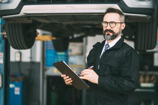 Автосервис и гараж автосервиса. портрет мужчины-менеджера бороды с бумагой контрольного списка в руке на концепции гаража ухода за автомобилем и автомобильного обслуживания.