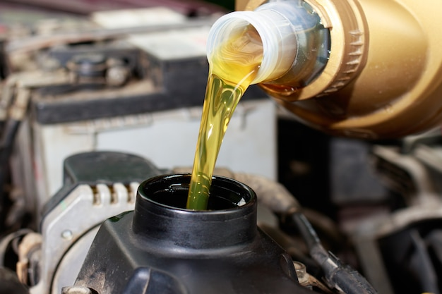 The car maintenance master pours engine oil for the car engine.