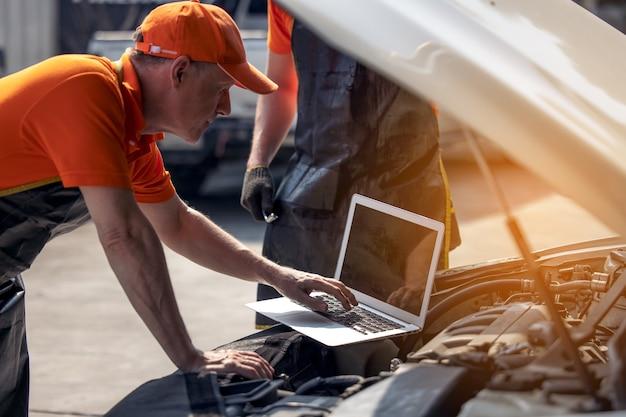 자동차 정비 서비스, 기술자는 노트북 컴퓨터로 자동차 엔진 고장 문제를 진단합니다.