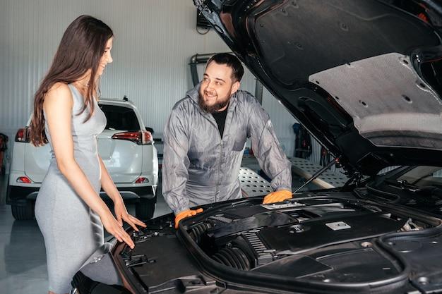 Автомеханик и клиент стоят рядом с обслуживаемым автомобилем