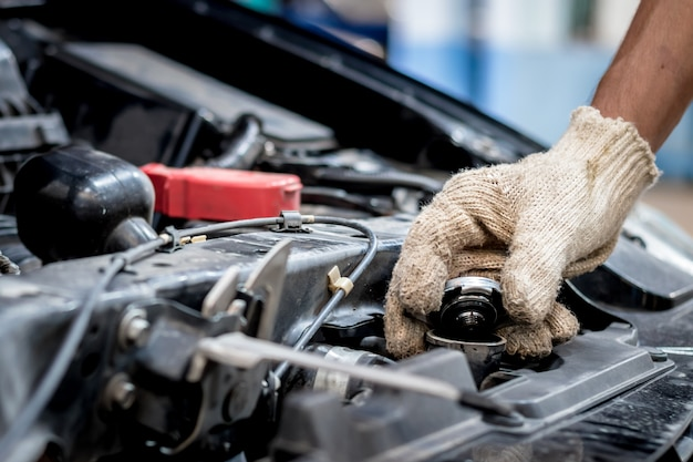 Car mechanic are opening the radiator cap