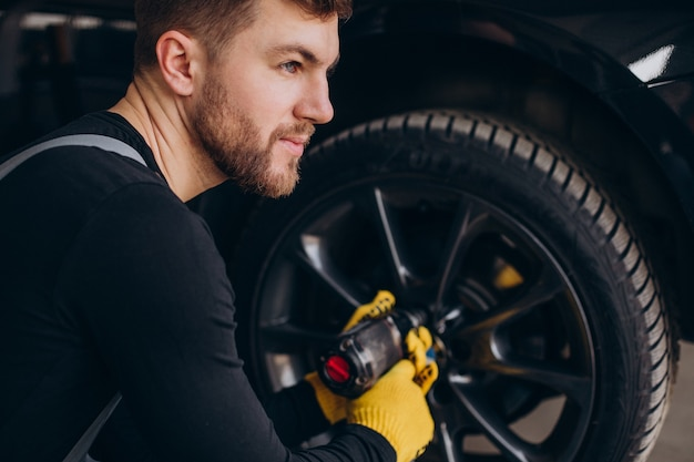 Car mechanic changing wheels in car