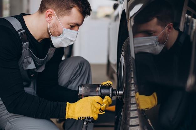 Car mechanic changing wheels in car