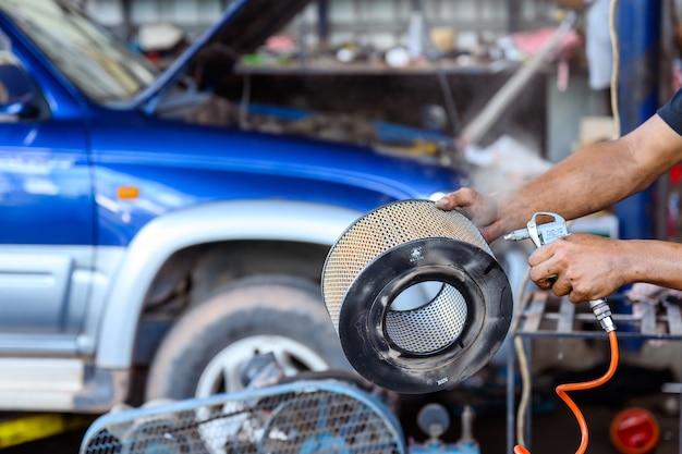 Car mechanic cleans and blows car air filter in car repair station.