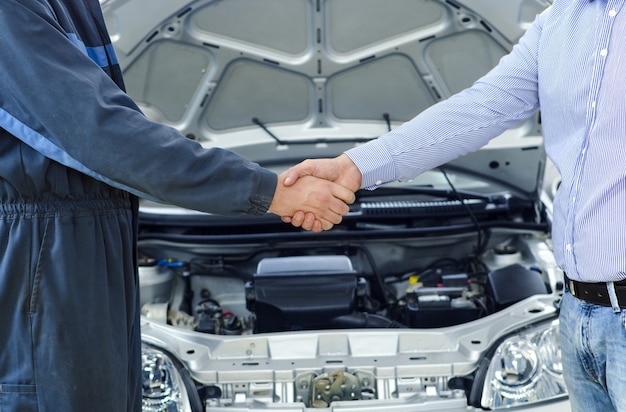 Car mechanic and customer shaking hands