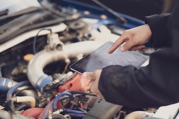 A car mechanic doing auto diagnostic using computer, searching for check engine