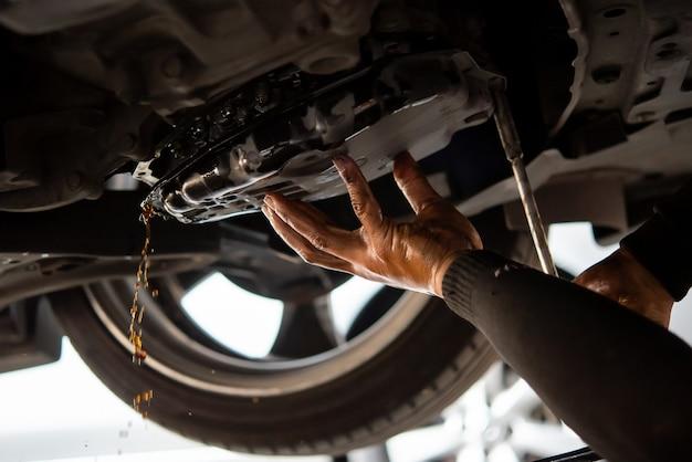 Автомеханик сливает старую трансмиссионную жидкость (atf) или трансмиссионное масло в гараже для замены масла в коробке передач двигателя автомобиля.