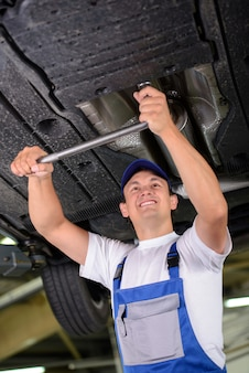 Car mechanic examining car suspension of lifted automobile.