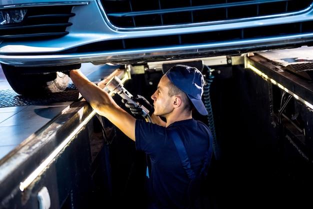 Автомеханик осматривает подвеску поднятого автомобиля на станции технического обслуживания