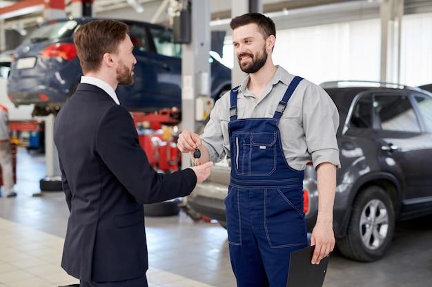 Car mechanic giving keys to businessman