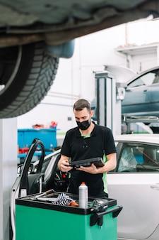 サージカルマスクを着用してクリップボードを保持し、メンテナンス車両をチェックする自動車整備士