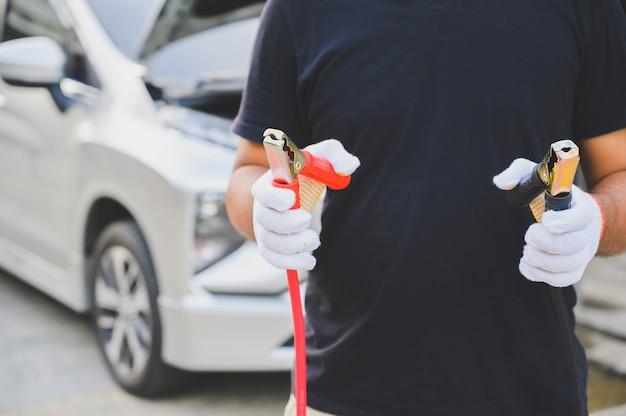 車のバッテリーを充電するための自動車整備士保持ジャンパーケーブル
