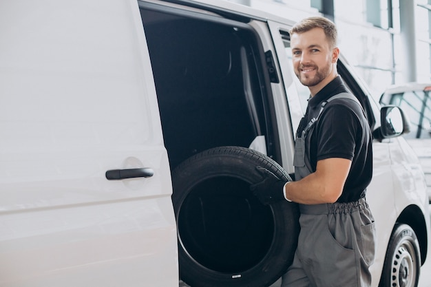 Car mechanic holding new tires by the white van