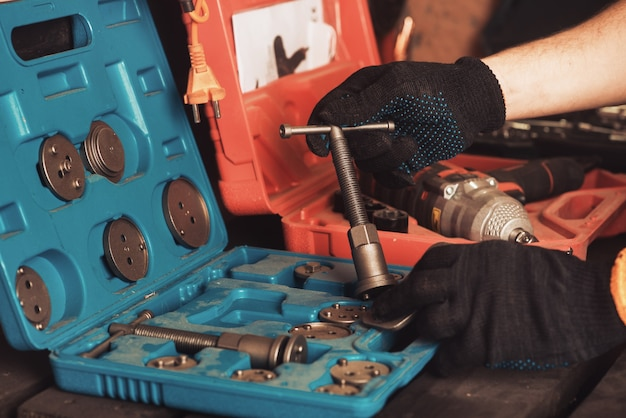 The car mechanic holds a special key in his hand for repairing the car. instrument boxing.