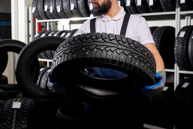 그의 직장에서 타이어의 스택에 워크샵에서 자동차 정비공, 손에 타이어를 들고 제복을 입은 젊은 남성