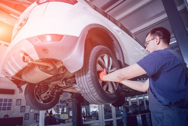 Car mechanic inspecting wheel and suspension detail of lifted automobile at repair service station