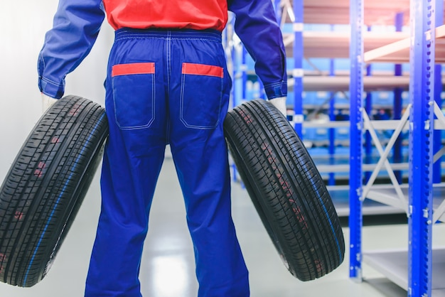 The car mechanic is changing new tires in stock to change for customers in the garage - changing wheels / tires.