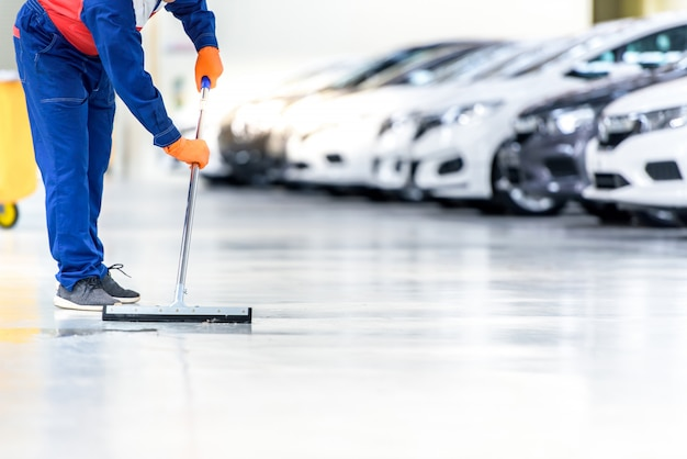 The car mechanic is cleaning, using a mop, rolling water from the epoxy floor. in the car service repair center