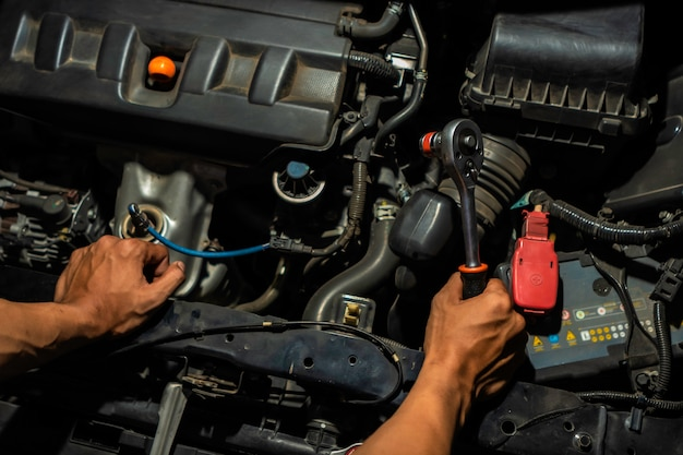 Car mechanic looking to the engine in the garage. service car motor repair.
