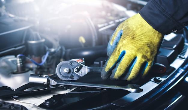 修理ガレージで車体のソケットレンチと工具を拾う自動車整備士