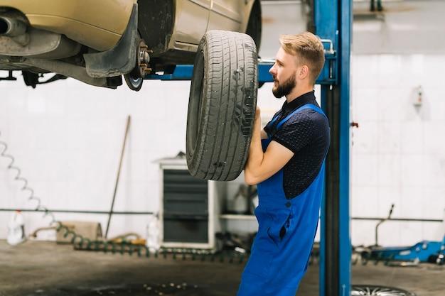 Car mechanic placing auto wheel ontransport nave