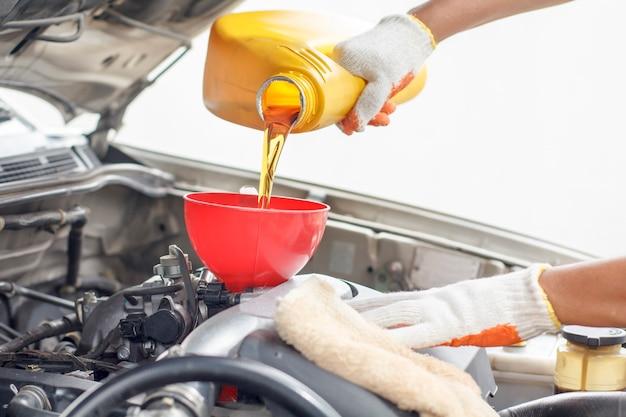 Автомеханик наливает новое масло в двигатель. Premium Фотографии