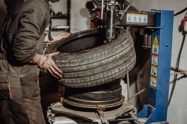 自動車整備士がタイヤ取り外し機械設備でリムからタイヤを取り外し、空気レンチがホイールのネジを緩めます
