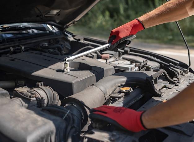 Автомеханик ремонтирует автомобильный двигатель с поднятым капотом и крупным планом инструмента