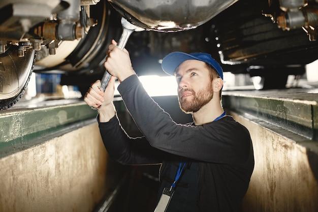自動車整備士がガレージで上昇中の青い車を修理します