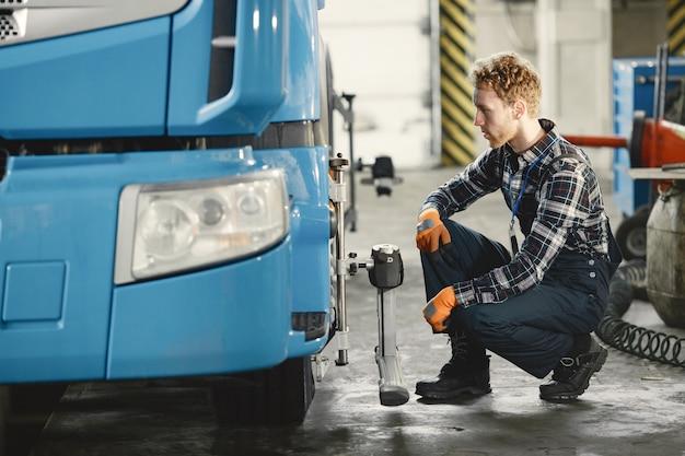 自動車整備士が工具を使ってガレージの車を修理