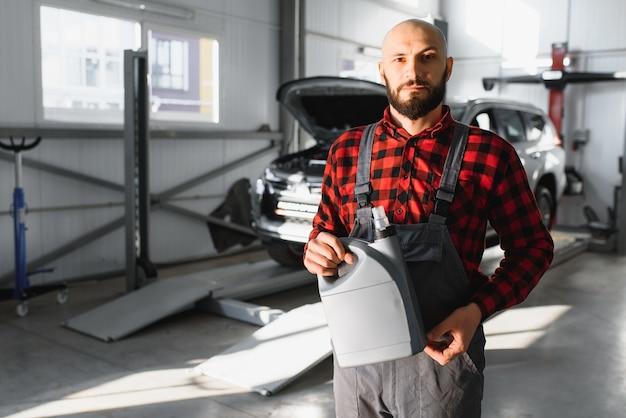 Автомеханик замены и заливки свежего масла в двигатель автомобиля