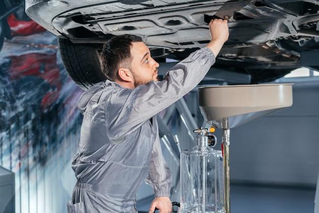 Car mechanic replacing oil in motor engine. auto service shop