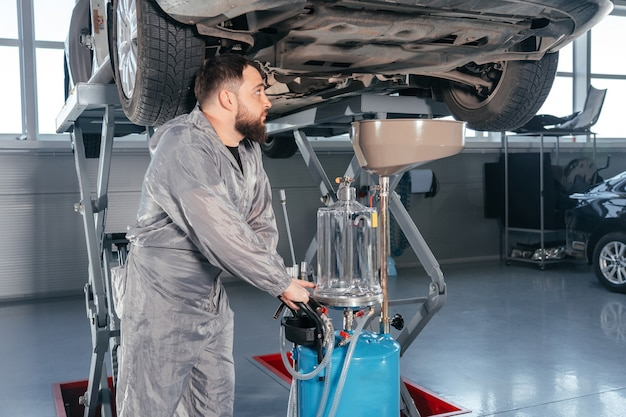 Car mechanic replacing oil in motor engine. auto service shop