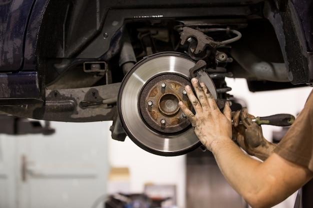 Car mechanic replacing pads for car break, transportation concept