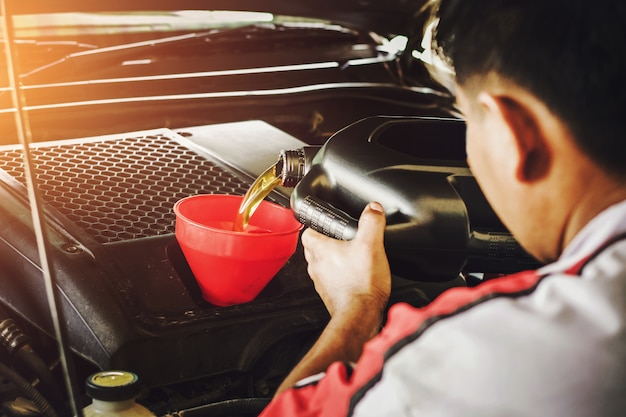 Car mechanic replacing with pouring oil into engine